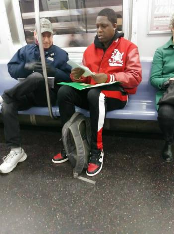 Người đàn ông áo đỏ đang xem bài tập toán của con trai, vô tình gặp thầy giáo ngồi cạnh. Ảnh:Denise Wilson