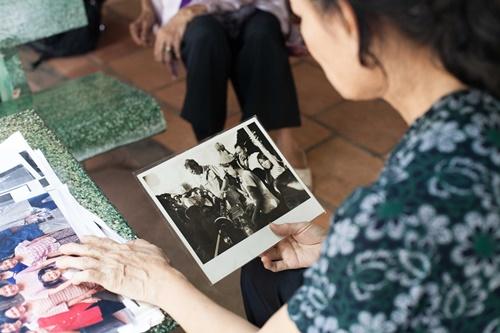 Bà Tròn lần giở lại những bức ảnh kỷ niệm với người nhiếp ảnh gia. Ảnh:Garry Michael Jones.