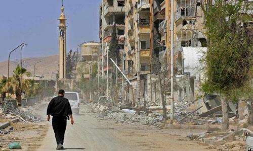 Một người đàn ông đi giữa những tòa nhà đổ nát ở ĐôngGhouta, thành phốDouma, ngoại ô thủ đôDamascus ngày 20/4. Ảnh: AFP.