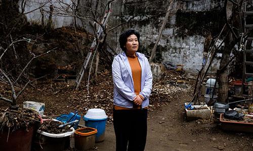 BàKim Ryon-hui đứng bên ngoài căn nhà ở Seoul, Hàn Quốc nơi bà sống chung với nhiều người Triều Tiên đào tẩu kháccó cùng mong muốn trở về quê nhà. Ảnh: Guardian.