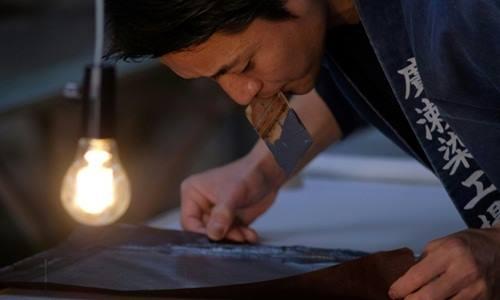 Yuichi Hirose giữ một mẩu giấy nến cắt tay để nhuộm màu cho bộ kimono trong một xưởng may lâu đời ở Tokyo. Ảnh: AFP.