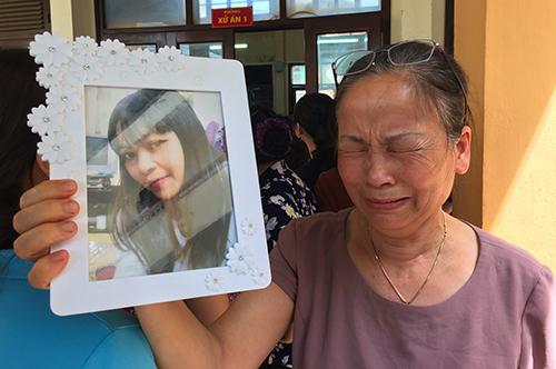Bà Nguyễn Thị Thu cầm di ảnh con đến dự phiên toà. Ảnh: Phạm Dự.