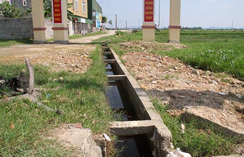 Nhà chức trách dự tính khi làm đường sẽ lấp mương nước chảy qua giữa cổng. Ảnh: Đức Hùng