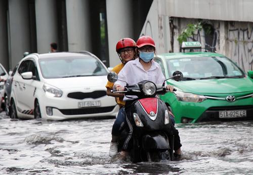 Xe máy của đôi bạn trẻ bị chết máy trong nước ngập. Ảnh: Duy Trần