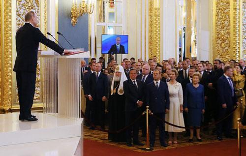 Thủ tướng Medvedev và các khách mời đứng sau hàng rào nhung khi ông Putin tuyên thệ. Ảnh: Reuters.