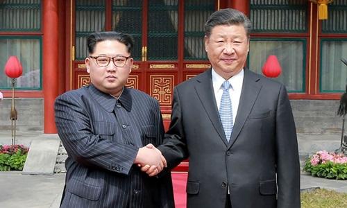 Lãnh đạo Triều Tiên Kim Jong-un tới thăm Trung Quốc và gặp người đồng cấp Tập Cận Bình hôm 27/3. Ảnh: AFP.