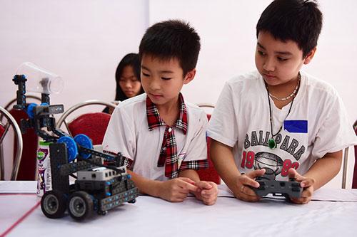 Các bạn nhỏ thích thú điểu khiển robot mang các vật nhẹ để sẵn trên bàn.