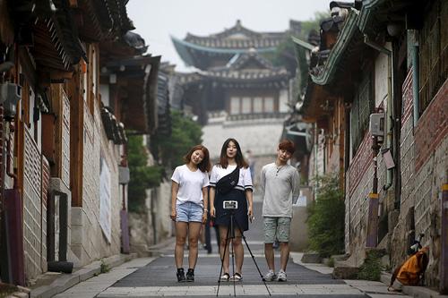 Thanh niên Hàn Quốc chụp ảnh tại làng Bukchon Hanok, thủ đô Seoul. Ảnh: Reuters.