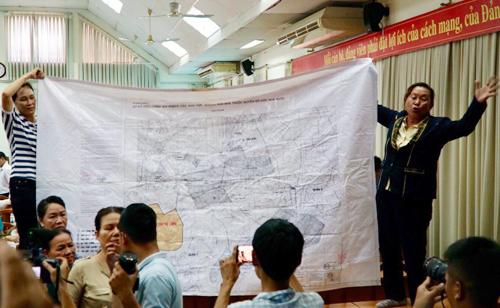 Người dân căng bản đồ quy hoạch Thủ Thiêm tại buổi tiếp xúc cử tri. Ảnh: Phạm Duy.