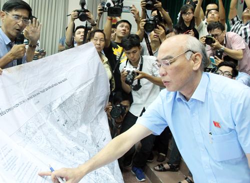 Ông Phan Nguyễn Như Khuê (Phó trưởng đoàn chuyên trách Đoàn đại biểu Quốc hội thành phố) xem bản đồ quy hoạch Thủ Thiêm không phần đất của dân nhưng vẫn bị thu hồi. Ảnh: Phạm Duy.