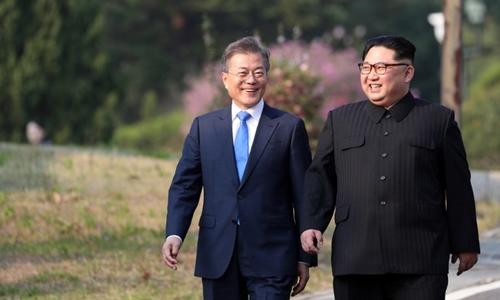 Tổng thống Hàn Quốc Moon Jae-in (trái) vàlãnh đạo Triều Tiên Kim Jong-un tản bộ sau khi trồng cây lưu niệm tại DMZ hôm 27/4. Ảnh: AFP.