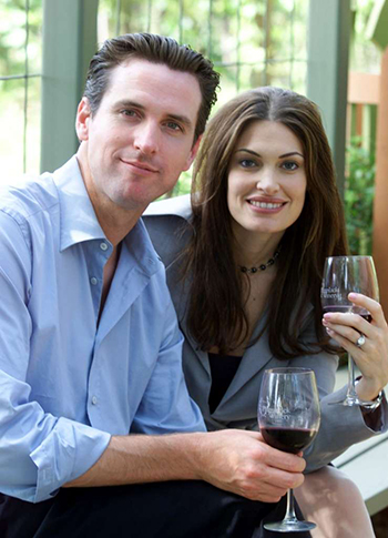 Gavin Newsom, left, and his wife, Kimberly Guilfoyle Newsom, right, pose for a picture at the PlumpJack winery in Oakville, Calif., Friday June 7, 2002.