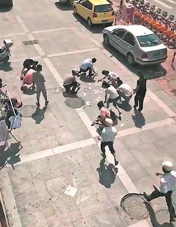 Người qua đường chạy tới nhặt tiền trên vỉa hè. Ảnh: Báo Tuyền Châu.