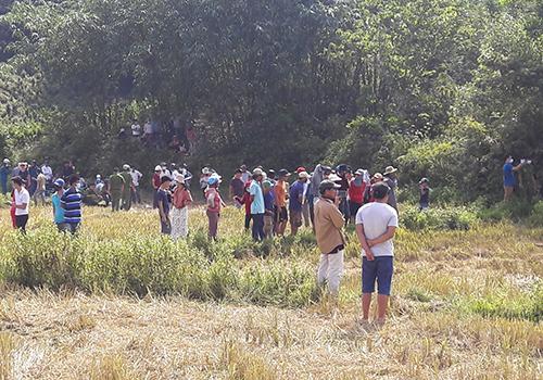 Người dân tập trung ở ruộng lúa theo dõi công an khám nghiệm tử thi. Ảnh: N.T.