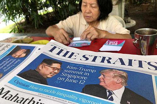 Một người bán hàng đếm tiền cạnh xấp báo in hìnhTổng thống Donald Trump hôm 10/5 tuyên bố ông sẽ gặp lãnh đạo Kim Jong-un