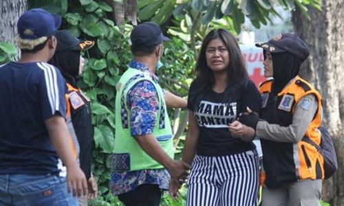 Cảnh sát Indonesia hỗ trợ một người dân bị thất lạc thân nhân sau vụ tấn công. Ảnh: Reuters.