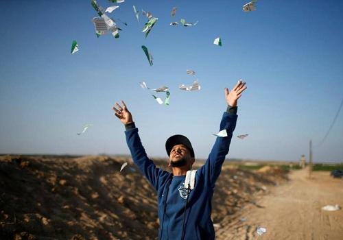 Một người Palestine xé những tờ rơi của quân đội Israel trong cuộc biểu tình nhằm chống lại việc Mỹ chuyển đại sứ quán tới Jerusalem ngày 14/5. Ảnh: Reuters.