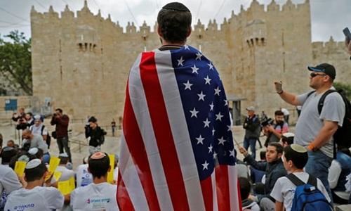 Một người đàn ông Israel khoác cờ Mỹ đứng bên ngoài Cổng Damascus ở Jerusalem hôm 13/5. Ảnh: AFP.