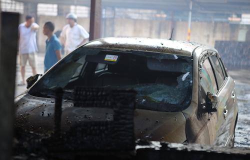 Xe ô tô để sát ki ốt bị cháy đen phần đầu. Ảnh: Nguyễn Hải.