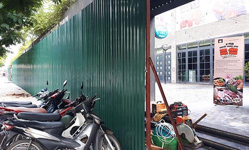Nhiều nhà hàng cố tình không di chuyển đồ đạc, quận Cầu Giấy đã lập hàng rào cao khoảng 3 m trước cửa. Ảnh: Phương Sơn