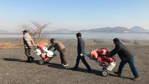 Các nhà hoạt động Hàn Quốc vận chuyển đồ tiếp tế tới mỏm đá gần Khu Phi quân sự. Ảnh: CNN.