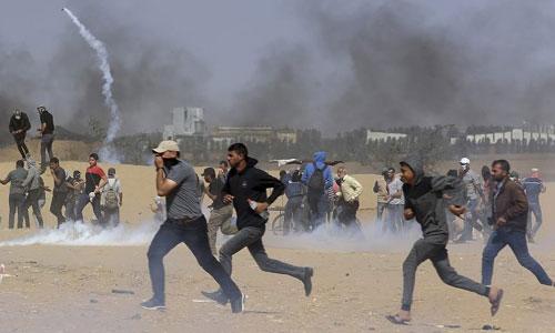 Người biểu tình Palestine tháo chạy khi lính Israel bắn đạn hơi cay. Ảnh: AP.