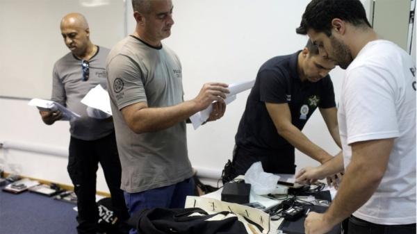 Cảnh sát kiểm tra máy tính ở Rio de Janero sau cuộc lục soát. Ảnh: Reuters.