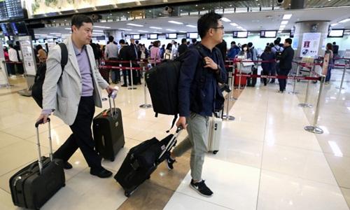 Các phóng viên Hàn Quốc làm thủ tục tại sân bay quốc tế Gimpo ở Seoul hôm nay trước khi đến Bắc Kinh, nơi họ sẽ tới Triều Tiên. Ảnh: Yonhap.