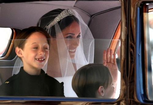 Hai anh em sinh đôi 7 tuổi nhàMulroney, con của bạn thân Meghan, giúp cô dâu nâng khăn voan trong lễ cưới. Ảnh: AFP.