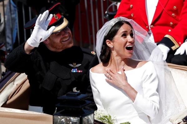 Hoàng tử Harry và vợ mới cưới trên xe ngựa, vẫy tay chào người ủng hộ tại Windsor, Anh, hôm 19/5. Ảnh: Reuters.