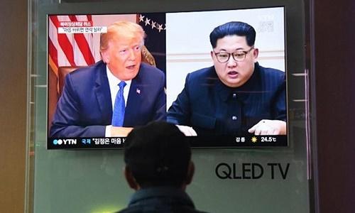 Một người dân theo dõi bản tin về Tổng thống Mỹ Donald Trump (trái) và lãnh đạo Triều Tiên Kim Jong-un ở Seoul hôm 25/5. Ảnh: AFP.