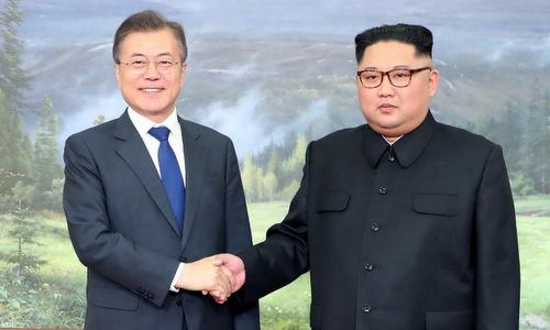 Tổng thống Hàn Quốc (trái) bắt tay lãnh đạo Triều Tiên trong cuộc gặp bất ngờ hôm 26/5. Ảnh: Yonhap.