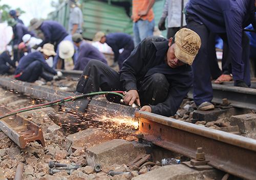 Công nhân sửa chữa đường ray bị hư hỏng. Ảnh: Đắc Thành.