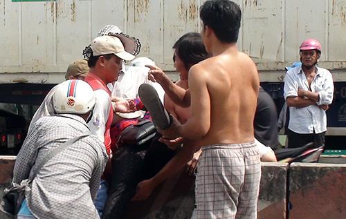 Người dân địa phương kéo người mắc kẹt trong vụ tainạn ra ngoài, đưa đi cấp cứu. Ảnh: Cửu Long