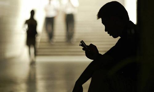 Một người đàn ông dùng điện thoại di động nhắn tin trong một đường hầm đi bộ ở Bắc Kinh, Trung Quốc. Ảnh: AFP.