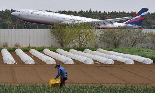 Một người nông dân chăm bón ruộng rau ngày 12/4 ngay cạnh đường băng của sân bayNarita, cửa ngõ quốc tế dẫn vào thủ đô Tokyo, Nhật Bản.Ảnh: AFP.
