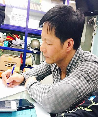 Ông Nguyễn Đức An viết trình báo tại công an. Ảnh: Như Thảo.