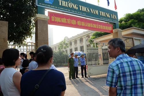 Phụ huynh đứng đợi cho cánh cổng trường Nam Trung Yên khép lại mới ra về. Ảnh: Quỳnh Trang.
