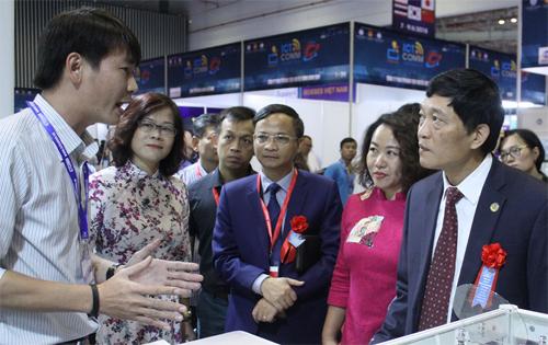 Thứ trưởng Trần Văn Tùng (bìa phải) vàkhách tham quan nghe giới thiệu công nghệ tại triển lãm. Ảnh: Ánh Tuyết.