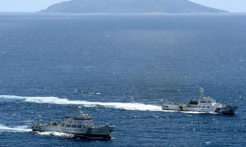 Tàu hải giám Trung Quốc (bên trái) di chuyển cạnh tàu cảnh sát biển Nhật Bản gần khu vực tranh chấp tại quần đảo Senkaku (Điếu Ngư) trên biển Hoa Đông. Ảnh: Kyodo.