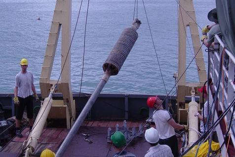 Các nhà khoa học đưa mẫu ống phóng đo trọng lực trên biển. Ảnh: PV Phách.
