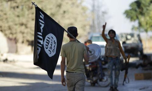 Một phiến quân mang theo cờ Nhà nước Hồi giáo (IS) tự xưng tại phía nam tỉnh Aleppo, Syria. Ảnh: Reuters.