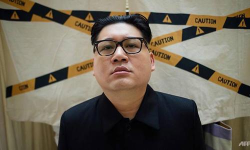 Howard X mặc trang phục và cắt tóc giống hệt Kim Jong-un chụp ảnh tại một trung tâm thương mại ở Hong Kong hôm 7/6. Ảnh: AFP.