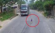 Tài xế hú vía khi bé trai băng qua đầu xe container