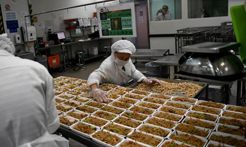 Nhân viên chuẩn bị suất ăn trong khu bếp của Sats. Ảnh: Straits Times.