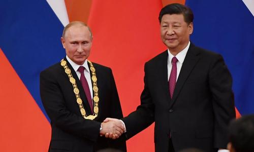Chủ tịch Trung Quốc Tập Cận Bình bắt tay với Tổng thống Nga Vladimir Putin sau khi trao Huân chương Hữu nghị. Ảnh: Reuters.