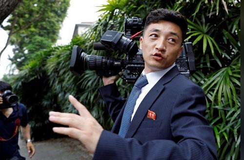 Một trong hai nhà báo Triều Tiên di chuyển tự do trên phố gần khách sạn St.Regis ở Singapore hôm 10/6. Ảnh: Reuters.