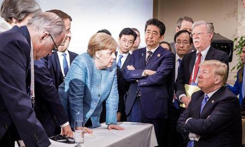 Trump ngồi khoanh tay, đối đầu các lãnh đạo G7. Ảnh: AFP.