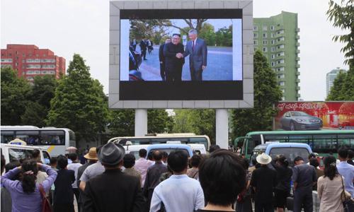 Người Triều Tiên theo dõi hình ảnh lãnh đạo Kim Jong-un bắt tay Thủ tướng Singapore Lý Hiển Long qua màn hình lớn tại ga tàu chính. Ảnh: AP.
