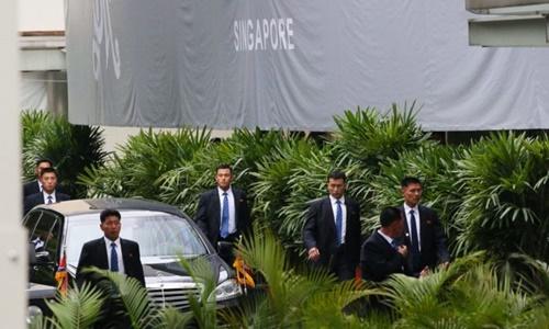 Cận vệ Triều Tiên chạy theo chiếc xe được cho là chở lãnh đạo Triều Tiên Kim Jong-un hướng về khách sạn St. Regis hôm nay. Ảnh:Straits Times.